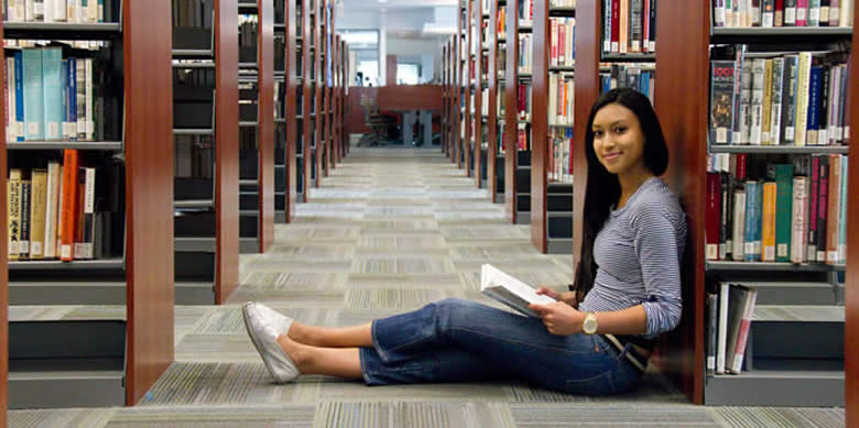 Girl sitting on floor of library with back up against book case