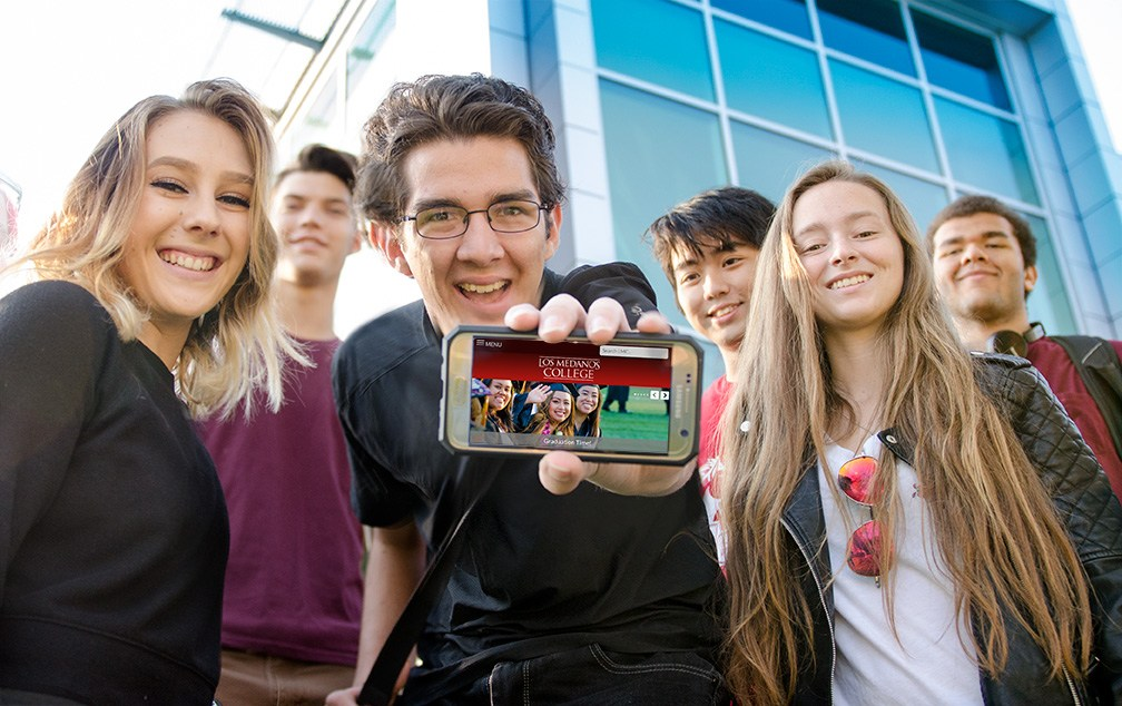 Students holding a smart phone showing the new respnsive website